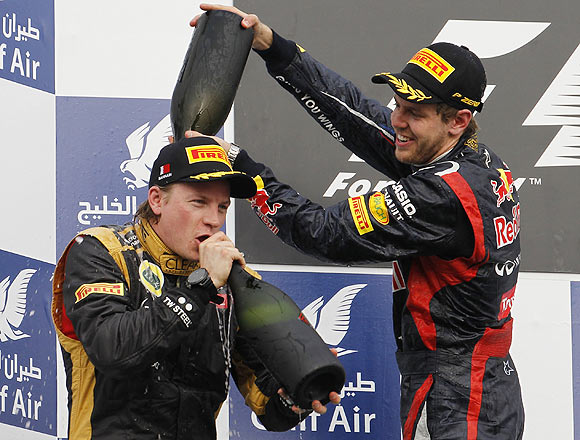 Red Bull's Sebastian Vettel pours champagne over second placed Lotus driver Kimi Raikkonen