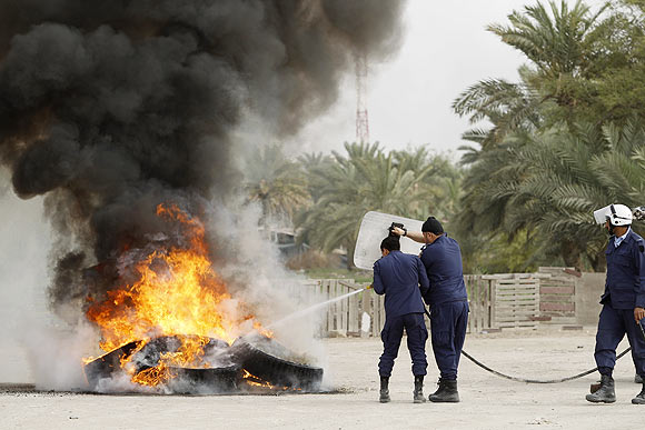 Riot police extinguish a fire during riots in Manama on Sunday