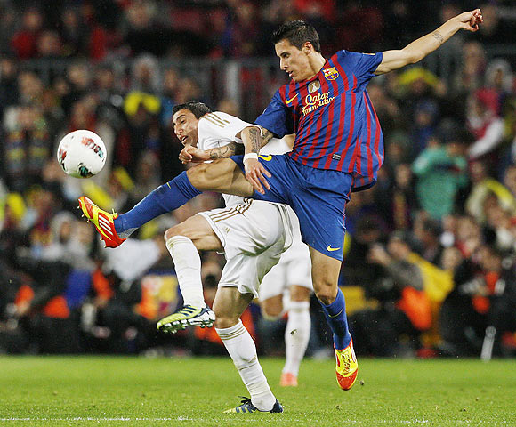 Real Madrid's Angel Di Maria (left) and Barcelona's Cristian Tello fight for possession