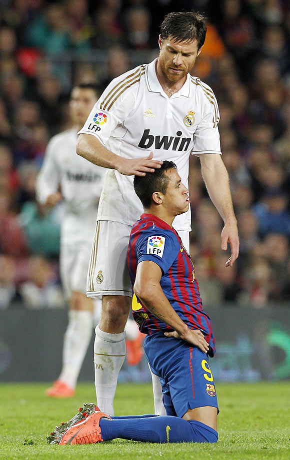 Real Madrid's Xabi Alonso comforts Barcelona's Alexis Sanchez after their El Clasico on Saturday
