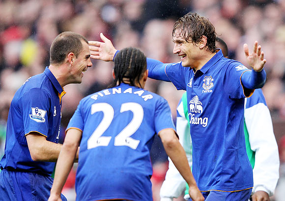Nikica Jelavic of Everton celebrates scoring the opening goal with team-mates Darron Gibson (left) and Steven Pienaar during the EPL match against Manchester United at Old Trafford on Sunday