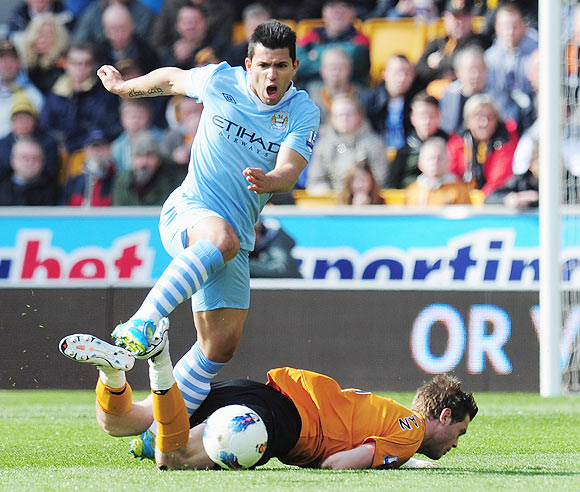 Sergio Aguero of Manchester City avoids a tackle from Richard Stearman of Wolverhampton Wanderers
