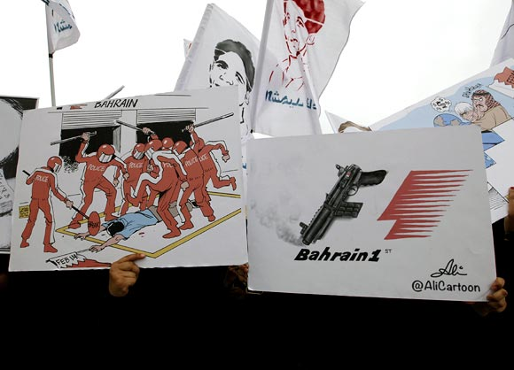 Anti-government protesters hold anti-F1 banners as they participate in a rally in village of Diraz, west of Manama