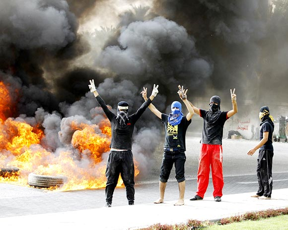 Anti-government protesters flash victory signs as they burn tyres in Budaiya, west of Manama