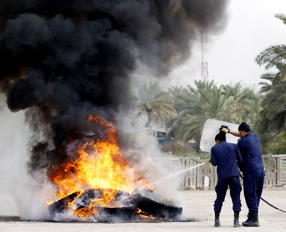 Riot police extinguish a fire during riots in Manama