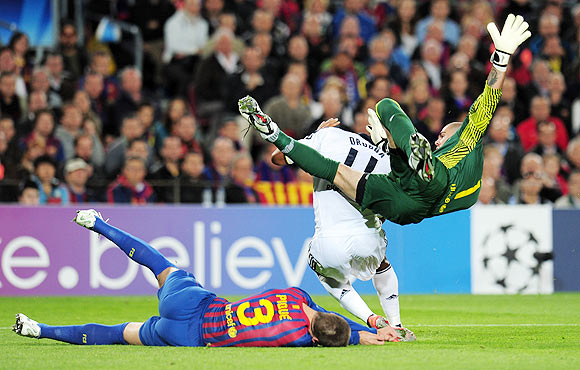 Gerard Pique goes to the ground after clashing with teammate and keeper Victor Valdes and Chelsea's Didier Drogba on Tuesday