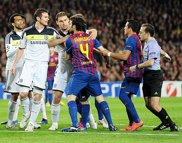Chelsea's Frank Lampard is controlled by teammates as he confronts Barca's Cesc Fabregas