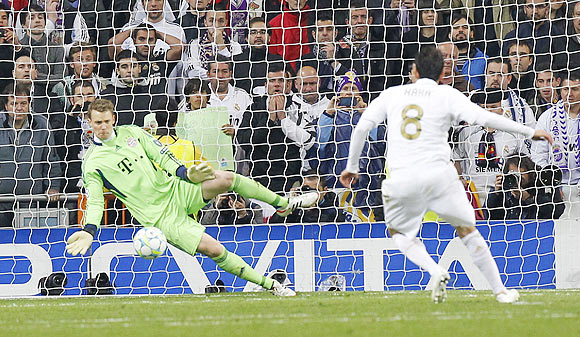 Real Madrid's Kaka (right) takes a penalty and fails to score past Bayern Munich's goalkeeper Manuel Neuer