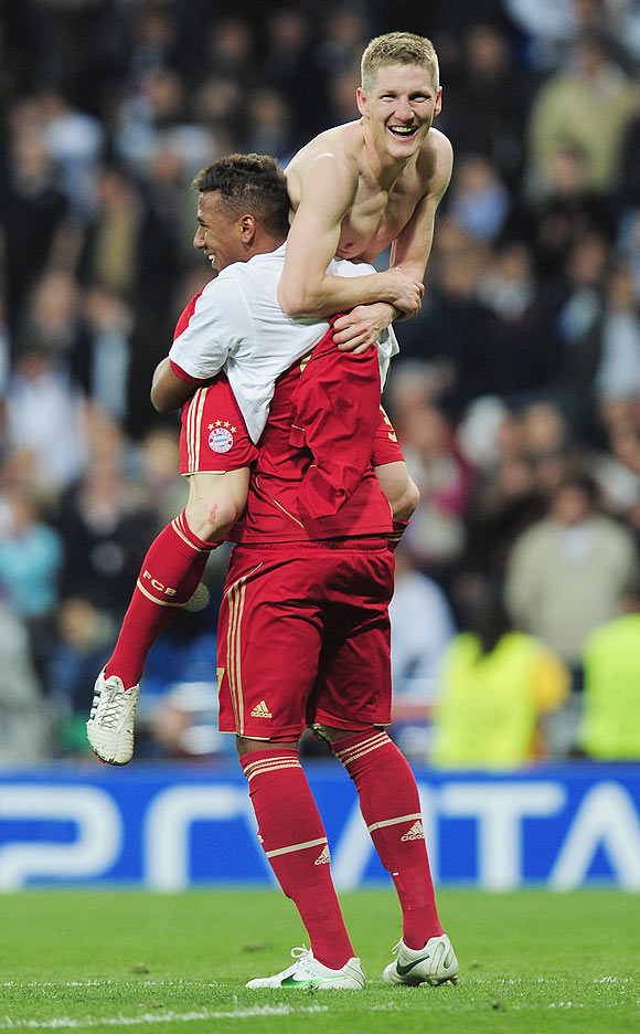 Bastian Schweinsteiger of Bayern Munich celebrates with teammate Jerome Boateng after scoring the winning penalty