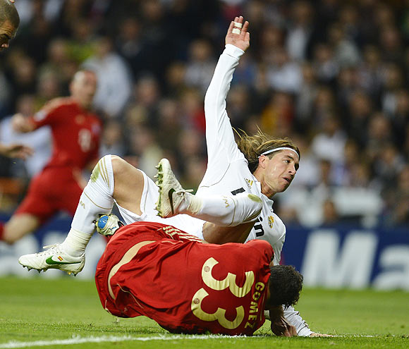 Bayern Munich's Mario Gomez is fouled by Real Madrid's Sergio Ramos to win a penalty