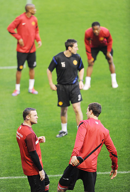 Wayne Rooney (left) of Manchester United speaks with his team-mate Jonny Evans as they excercise during a training session
