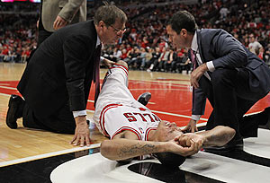 Derrick Rose of the Chicago Bulls is examined after suffering an injury against the Philadelphia 76ers in Game One of the Eastern Conference quarter-finals on Saturday
