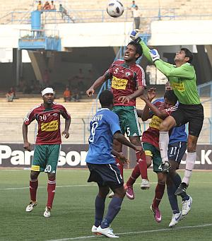 Mohun Bagan goalkeeper Shilton Pal (in green) fists a Dempo attack at the Salt Lake Stadium on Sunday