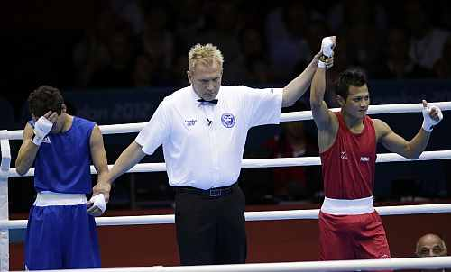 India's Devendro Singh, right, reacts after defeating Honduras' Bayron Molina Figueroa during a light flyweight 49-kg preliminary boxing match