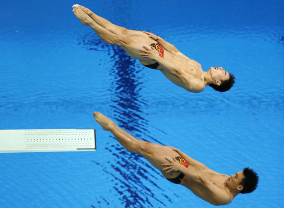 China's Luo Yutong and Qin Kai (top), who won gold, perform a dive during the men's synchronised 3m springboard final