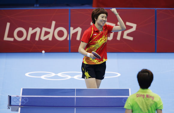 China's Li Xiaoxia celebrates a point against China's Ding Ning in their women's singles gold medal table tennis match