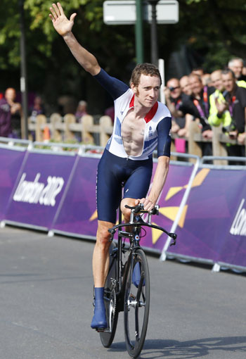 Britain's Bradley Wiggins raises his hand as he takes a victory lap after winning the men's cycling individual time trial
