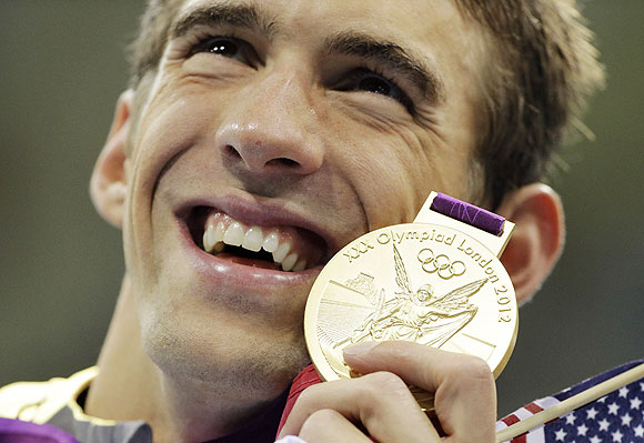 United States' Michael Phelps poses with his gold medal after the men's 4x200-meter freestyle relay swimming final at the Aquatics Centre in the Olympic Park on Tuesday