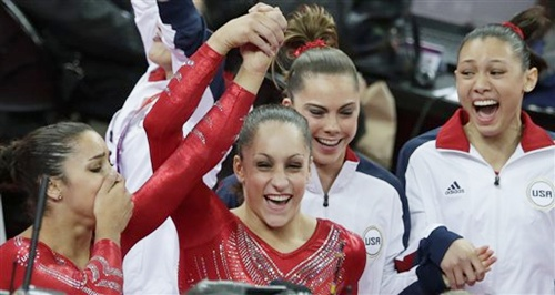 US gymnast Jordyn Wieber, second left, lifts up the hand of teammate Alexandra Raisman, as they celebrate along with McKayla Maroney and Kyla Ross after being declared winners of the gold medal
