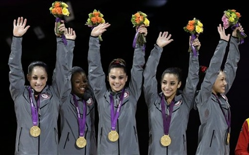 US gymnasts, left to right, Jordyn Wieber, Gabrielle Douglas, McKayla Maroney, Alexandra Raisman, Kyla Ross raise their hands on the podium