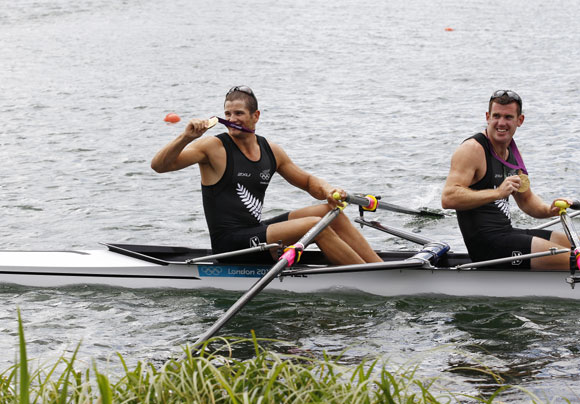 New Zealand's Nathan Cohen (back) and Joseph Sullivan smile with their gold medals at the victory ceremony after winning the men's double sculls finals rowing event