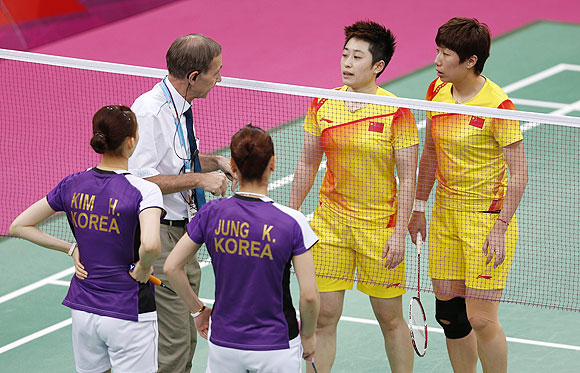 Tournament referee Torsten Berg (2nd L) speaks to players from China and South Korea during their women's doubles group play stage Group A badminton match during the London 2012 Olympic Games at the Wembley Arena on Tuesday