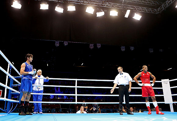 Ali Mazaheri of Iran (left) refuses to stand with the referee for his decision of a victory to Jose Gomez Larduet of Cuba during the Men's Heavy (91kg) boxing event on at the London Olympic Games on Wednesday
