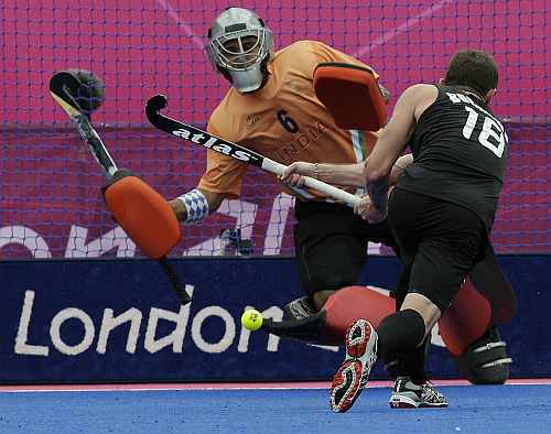 New Zealand's Phillip Burrows (18) scores a goal on a penalty as goalkeeper Bharat Kumar Chetri fails to save it during their men's hockey preliminary match