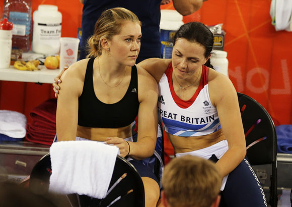 Britain's Victoria Pendleton (R) and Jessica Varnish react after being disqualified after the track cycling women's team sprint qualifying heats at the Velodrome