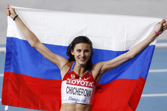 Anna Chicherova of Russia holds her national flag after winning the gold medal in the women's high jump final at the IAAF World Athletics Championships in Daegu