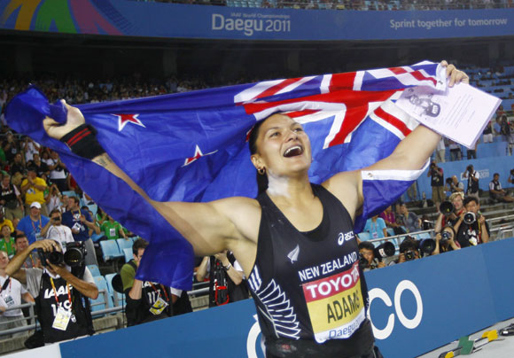 Valerie Adams of New Zealand holds her national flag after winning the women's shot put final at the IAAF World Championships in Daegu