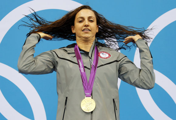 Rebecca Soni of the U.S. flips her hair as she poses with her gold medal in the women's 200m breaststroke victory ceremony