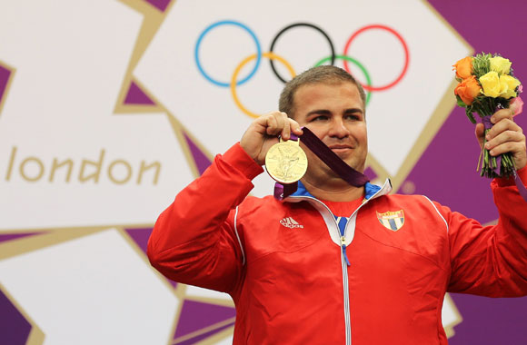 Cuba's Leuris Pupo poses with his gold medal won in the men's 25m rapid fire pistol shooting event