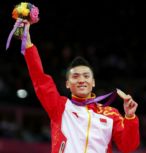 Dong Dong of China celebrates with his gold medal at the men's gymnastics trampoline final in the North Greenwich Arena