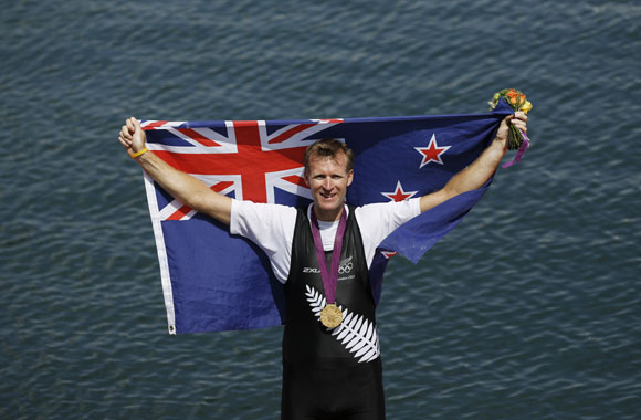 Gold medallist Mahe Drysdale of New Zealand holds up his national flag after the Men's Single Sculls Final event