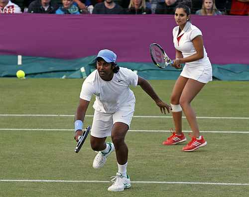 Leander Paes, left, returns a shot as he plays a mixed doubles match with playing partner Sania Mirza, right, at the All England Lawn Tennis Club at Wimbledon