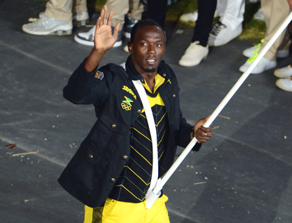 Reigning Olympic Men's 100m and 200m champion Usain Bolt of the Jamaica Olympic athletics team carries his country's flag during the Opening Ceremony of the London Games