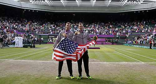 Gold medalists Mike Bryan, right, and Bob Bryan, left, of the United States, pose with the U.S. national flag after the medal ceremony of the men's doubles final match