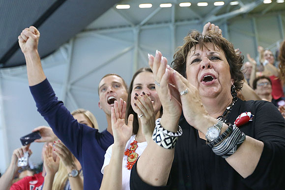 Michael Phelps's mother Debbie Phelps (right) and his sister Hilary Phelps (center) applaud as Michael Phelps of the United States receives gold medal