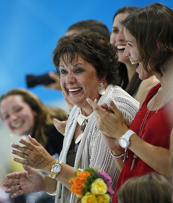 Debbie Phelps, left, and Whiney, right, mother and sister respectively of United States' Michael Phelps, applaud