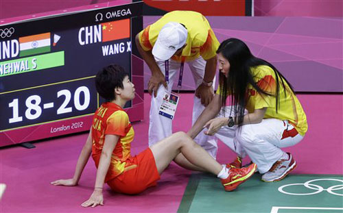 China's Wang Xin is looked at by team officials as she sits down in pain while playing against India's Saina Nehwal in a women's singles badminton bronze medal match