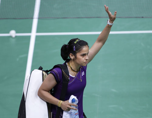 India's Saina Nehwal leaves the court after China's Wang Xin, unseen, retired hurt at the women's singles badminton bronze medal match