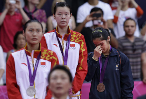 India's Saina Nehwal, right, in tears as she stands at themedal podium for winning bronze in women's singles badminton