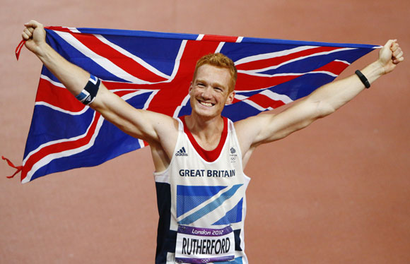 Britain's Greg Rutherford holds the Union Flag after winning the gold in the men's long jump final