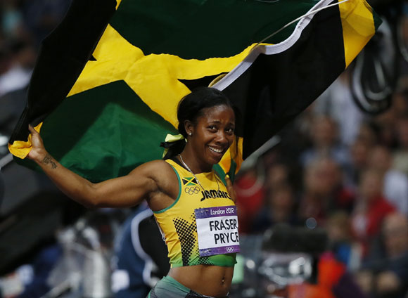 Jamaica's Shelly-Ann Fraser Pryce celebrates with her national flag after winning the women's 100m final