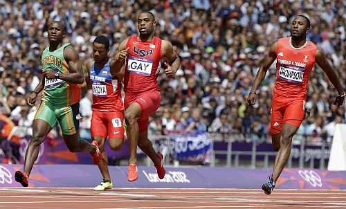 United States' Tyson Gay crosses the finish with Trinidad's Richard Thompson, right, and Zambia's Gerald Phiri, left, in a men's 100-meter heat