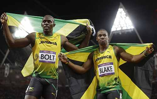 Jamaica's Usain Bolt, left, celebrates winning gold alongside silver medallist Yohan Blake of Jamaica following the men's 100-metre final