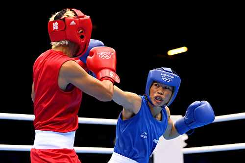 Mary Kom (Blue) of India competes against Maroua Rahali (Red) of Tunisia during the Women's Fly (51kg) Boxing Quarter-finals