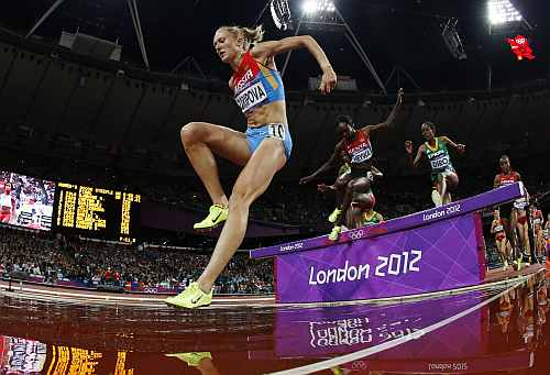 Russia's Yuliya Zaripova, left, goes to land in the water pit as she competes to win gold in the women's 3000-meter steeplechase final