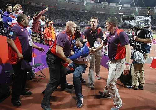 A spectator is detained by security after a beer bottle was thrown on to the track during the start of the men's 100 metres final